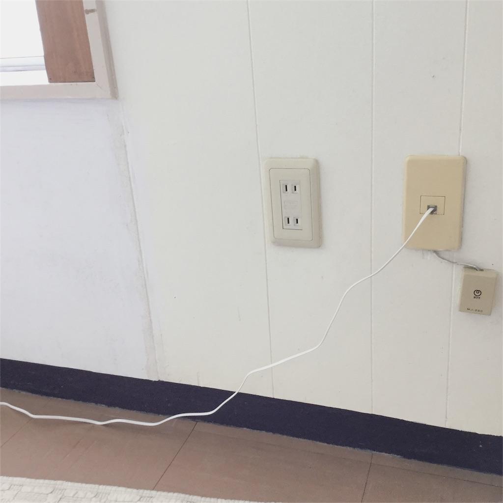 ネット回線のモデムにつないでいる電話線がだらしなく垂れている様子