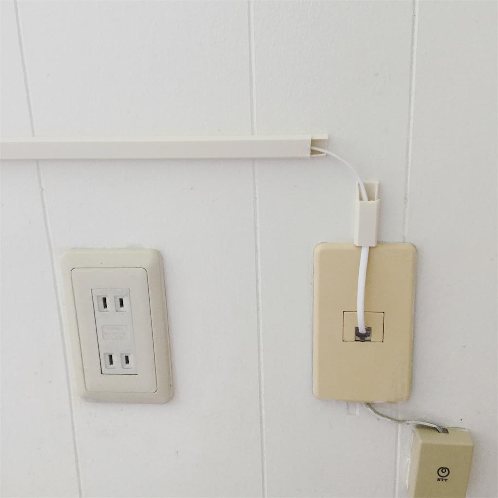 壁に固定した配線モールの下部分を少しずつはめていく